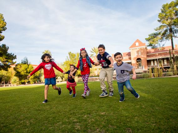 children playing out on the grass in front of Old Main